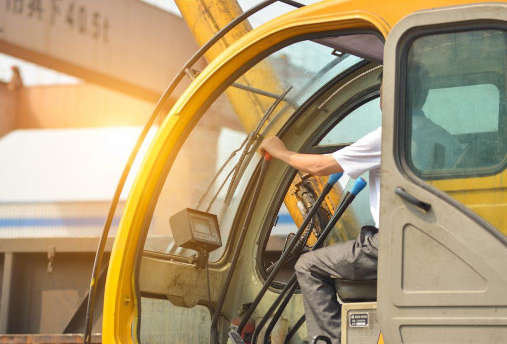 pro-suma.com man driving a crane to lift-up some equipments